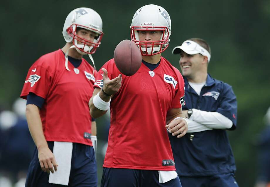 So that's the new guy:Tom Brady (left) talks with offensive coordinator Josh   McDaniels on Tim Tebow's first day at Patriots training camp in Foxborough, Mass. Photo: Charles Krupa, Associated Press