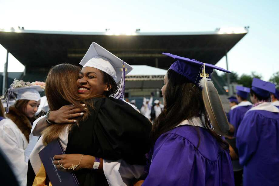 A graduate holds her diploma as she hugs one of her teachers during the James A. Garfield High School commencement ceremony at Memorial Stadium on Tuesday, June 11, 2013.  Nearly 400 students graduated in the high school's 128th graduation ceremony. Photo: LINDSEY WASSON, SEATTLEPI.COM / SEATTLEPI.COM