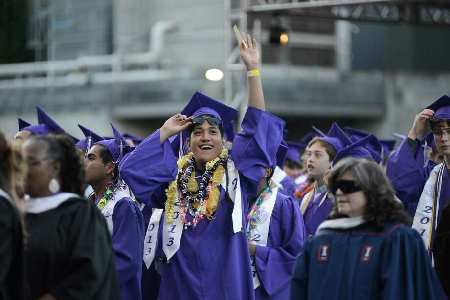 A senior waves at his family during the James A. Garfield High School commencement ceremony at Memorial Stadium on Tuesday, June 11, 2013.  Nearly 400 students graduated in the high school's 128th graduation ceremony. Photo: LINDSEY WASSON, SEATTLEPI.COM / SEATTLEPI.COM