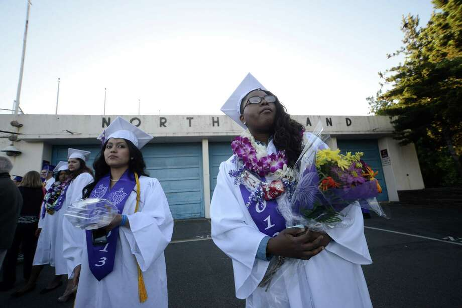 Katherine Medrano, left, and Essence Partee, right, wait for Katherine's dad before the James A. Garfield High School commencement ceremony at Memorial Stadium on Tuesday, June 11, 2013.  Nearly 400 students graduated in the high school's 128th graduation ceremony.  Photo: LINDSEY WASSON, SEATTLEPI.COM / SEATTLEPI.COM