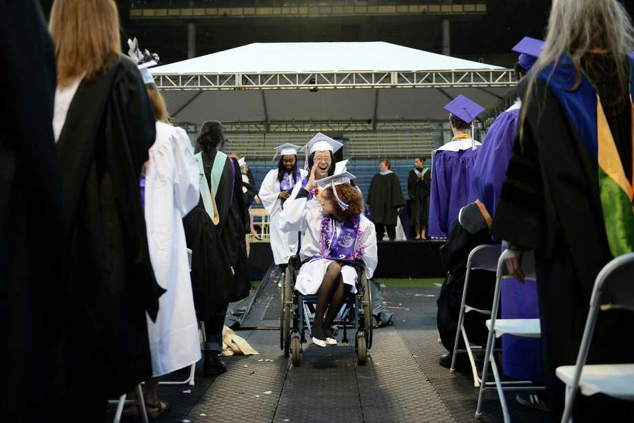 Irene Chauncey holds onto her cap as she is wheeled down the main drag during the James A. Garfield High School commencement ceremony at Memorial Stadium on Tuesday, June 11, 2013.  Nearly 400 students graduated in the high school's 128th graduation ceremony. Photo: LINDSEY WASSON, SEATTLEPI.COM / SEATTLEPI.COM