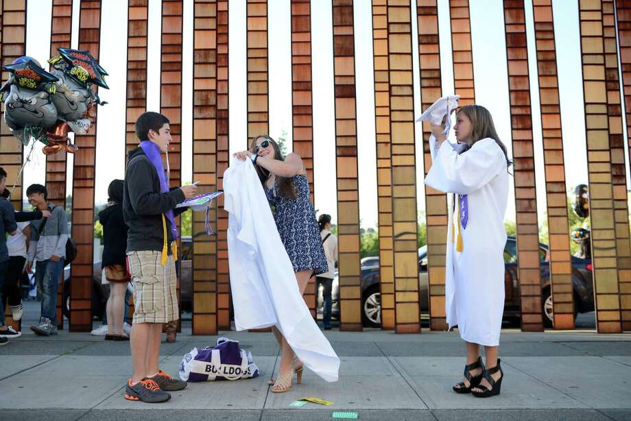 Caleb Zatto, Laura Bogaard, and Anita Yuranets rush to put on their caps and gowns outside the EMP before the James A. Garfield High School commencement ceremony at Memorial Stadium on Tuesday, June 11, 2013.  Nearly 400 students graduated in the high school's 128th graduation ceremony. Photo: LINDSEY WASSON, SEATTLEPI.COM / SEATTLEPI.COM