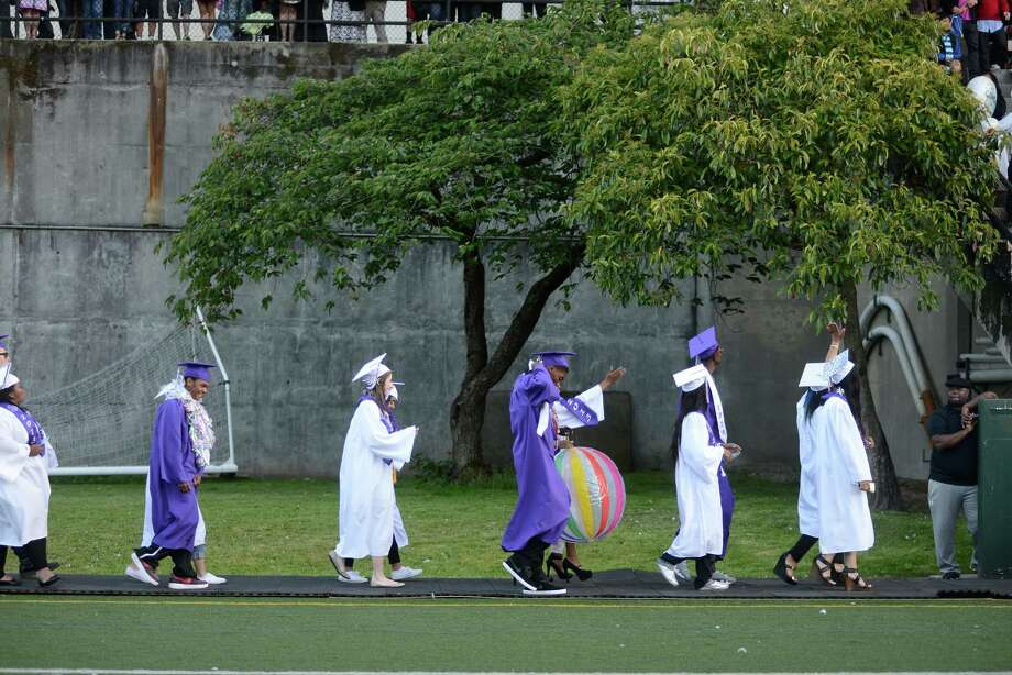 Graduates carry a beach ball into the stadium during the James A. Garfield High School commencement ceremony at Memorial Stadium on Tuesday, June 11, 2013.  Nearly 400 students graduated in the high school's 128th graduation ceremony. Photo: LINDSEY WASSON, SEATTLEPI.COM / SEATTLEPI.COM