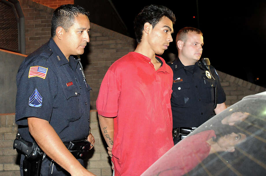 Rogelio Arellano Torres is escorted to a waiting police vehicle after being arrested for carjacking at the Beaumont Police Department in Beaumont, Wednesday, June 27, 2012. Tammy McKinley/The Enterprise Photo: TAMMY MCKINLEY