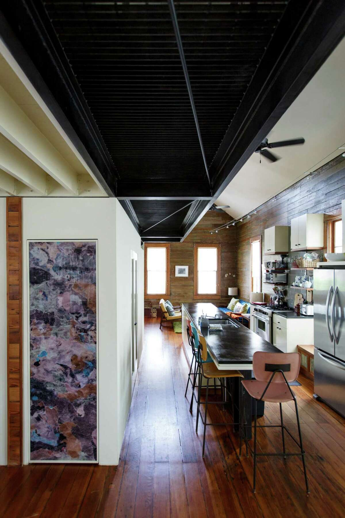 The open kitchen area in David Ansell and his wife Bennie Flores Ansell's Sixth Ward home inlcudes a personalized photo over the pantry door by artist Linda Hayward. ( Michael Paulsen / Houston Chronicle )