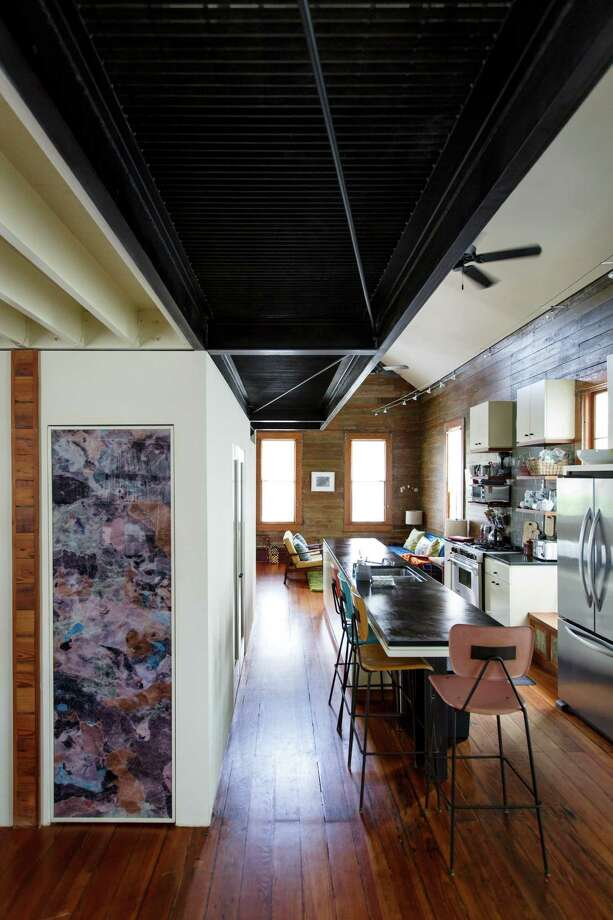 The open kitchen area in David Ansell and his wife Bennie Flores Ansell's Sixth Ward home inlcudes a personalized photo over the pantry door by artist Linda Hayward. ( Michael Paulsen / Houston Chronicle ) Photo: Michael Paulsen, Staff / © 2013 Houston Chronicle