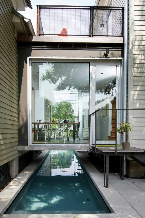 The glass-enclosed dining room connects the original 1885 cottage with the houselike addition as it hovers over the swimming pool. Photo: Michael Paulsen, Staff / © 2013 Houston Chronicle