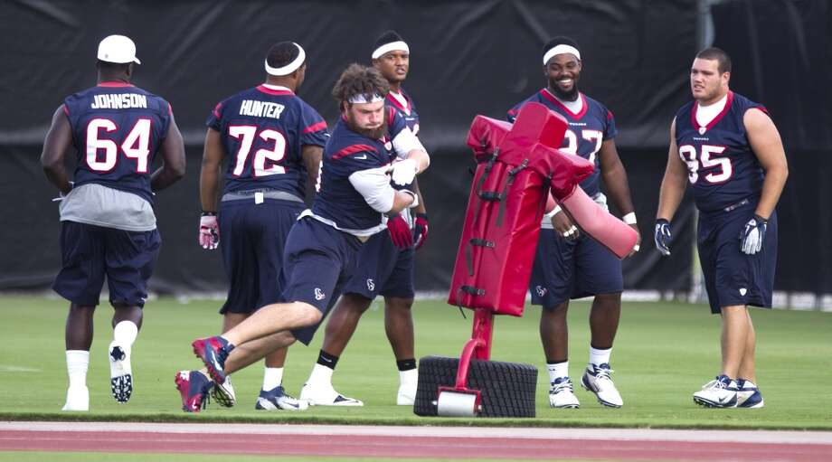 Defensive end Jared Crick, center, runs through a blocking dummy with the rest of the defensive linemen. Photo: Brett Coomer, Chronicle
