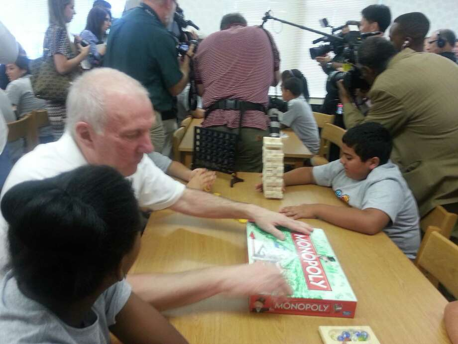 Coach Pop playing Monopoly with Wheatley students in the new NBA Cares Learn & Play Center. Photo: Nora Lopez/Express-News