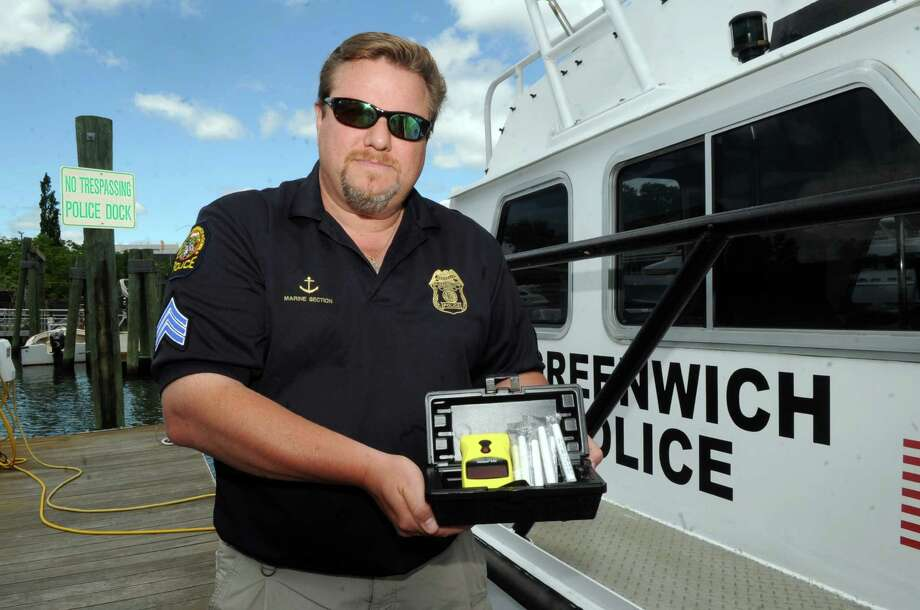 Sgt. David Nemecek holds an Intoxilyzer standing on a dock near one of the Greenwich Police boats in Greenwich, Conn., Wednesday, June 12, 2013. Police are going to conduct drunk driving stops this month - on the water, going after drunken boaters. Photo: Helen Neafsey / Greenwich Time