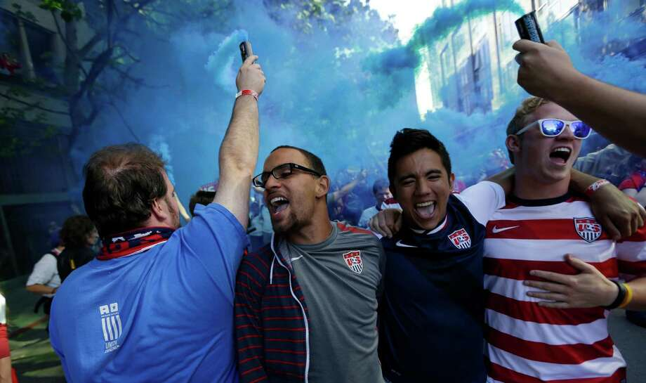 USA supporters carry smoke devices as they sing while marching to a World Cup qualifier soccer match against Panama, Tuesday, June 11, 2013, in Seattle. Photo: Ted S. Warren, AP / AP