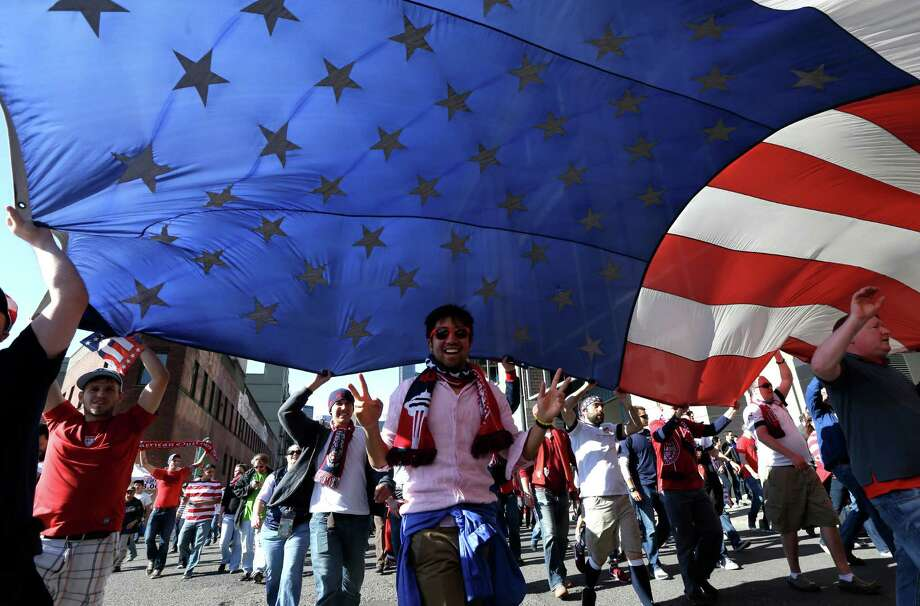 USA supporters carry a large flag as they march to a World Cup qualifier soccer match against Panama, Tuesday, June 11, 2013, in Seattle. Photo: Ted S. Warren, AP / AP