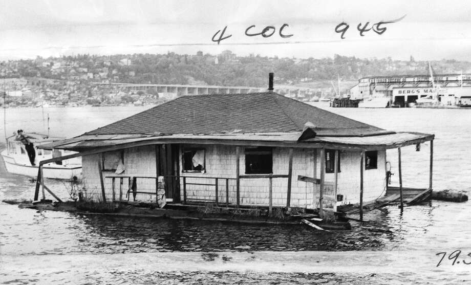 The unromantic side of houseboats: This 1962 photo shows a Seattle police boat towing a crumbling, abandoned houseboat set adrift in a windstorm on Lake Union. 