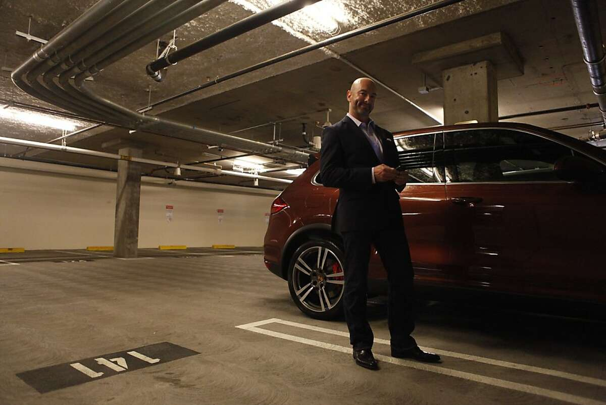 Sean Sullivan, San Francisco realtor, poses for a portrait in the $82,000 parking space he recently sold in the parking garage on 88 Townsend St. The parking spot is number 142, which is now home to a Porsche that belongs to the new owner.