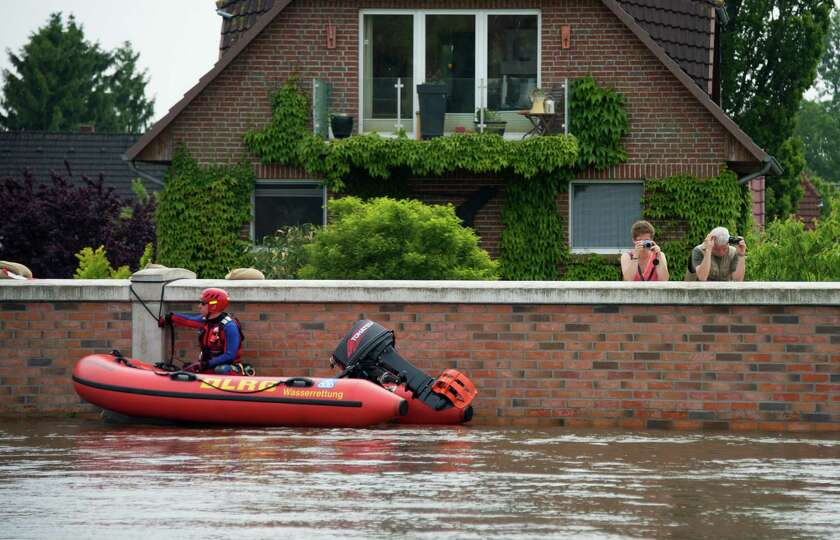 People take pictures of the water next to a man on a rescue boat as houses are flooded  in Hohnstorf
