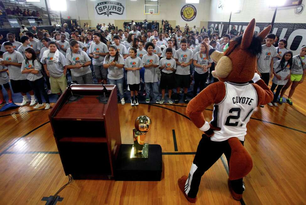 The Spurs' Coyote interacts Wednesday, June 12, 2013, with students at Wheatley Middle School before the start of an NBA Cares event at the school.