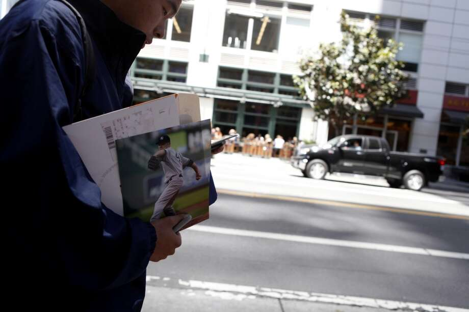 A New York Yankee's fan carries photos to get signed outside of the St. Regis Hotel.  Fans gather while the team is in town hopes of meeting and getting autographs from the players on Wednesday.