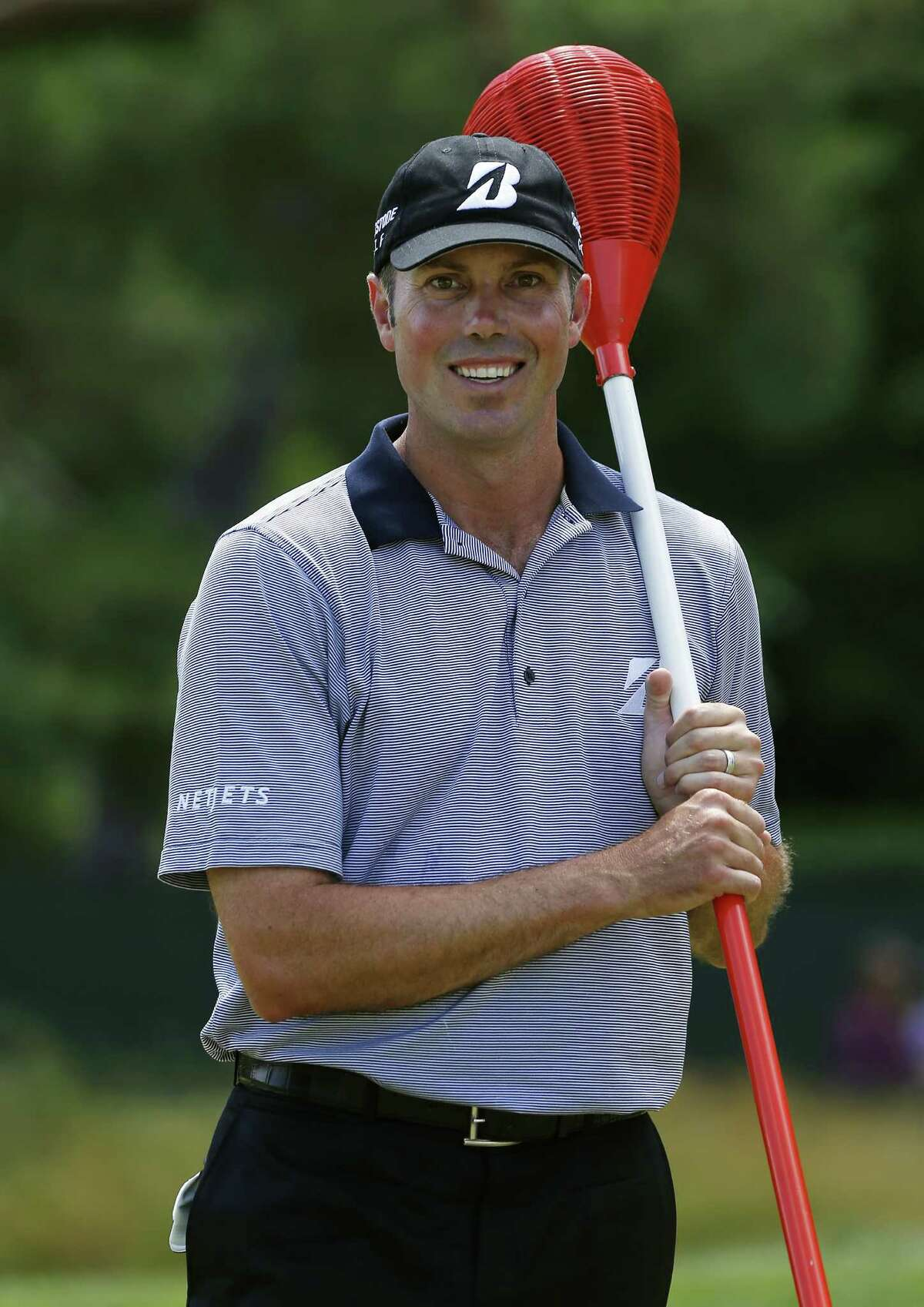 The seemingly ever-smiling Matt Kuchar clowns around with one of Merion's wicker basket flagsticks.