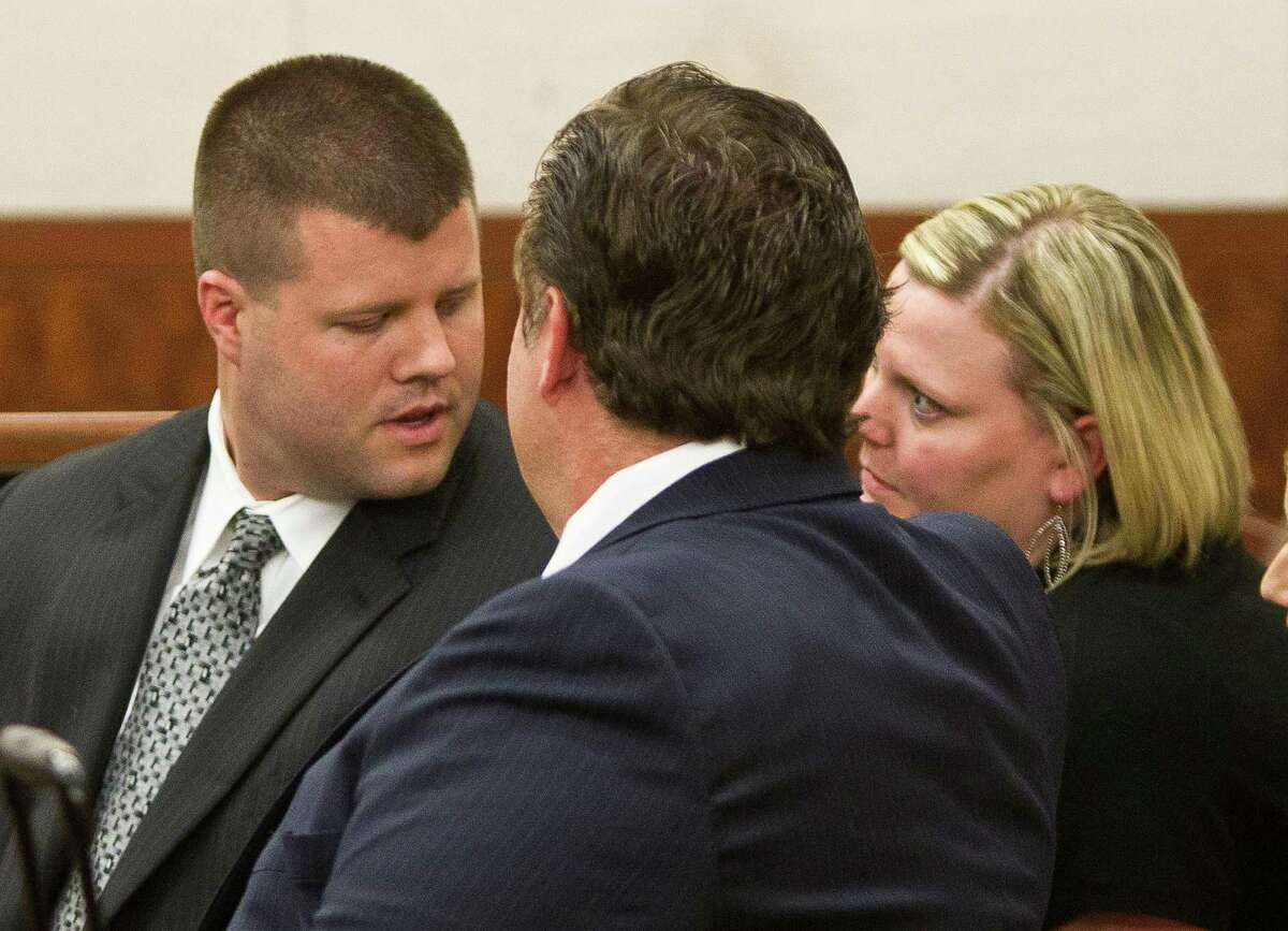 Ex-Houston Police officer Drew Ryser, left, talks to his wife, Allison, after Judge Ruben Guerrero read his guilty verdict for official oppression in the Chad Holley case.
