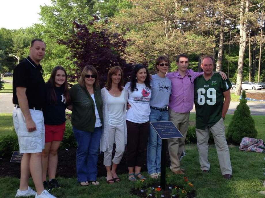 Families of Christopher Stewart, Deanna Rivers, Luke Romano and Nick Cammarata attend a June 5 ceremony to rededicate the Shenendehowa Memorial Garden. The families formed a committee to transform the garden in front of the high school into a place where students can reflect on students and teachers who recently died while attending school. The restoration includes new grass, bushes, a tree and stepping stones. Each family also bought a stone bench. (Regina Stewart)