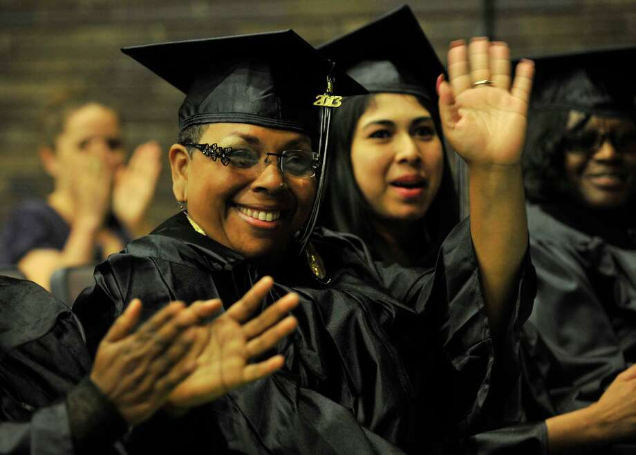 Graduate Nancy Flores waves to her son, Jeremy, who is the National External Diploma Program student speaker at the adult and continuing education commencement ceremony at Cloonan Middle School in Stamford on Wednesday, June 12, 2013. Photo: Jason Rearick / Stamford Advocate
