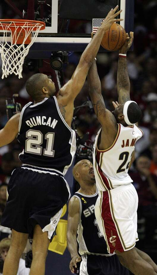 The Spurs' forward Tim Duncan (21) with help from forward Bruce Bowen (12) manages to block Cavaliers forward LeBron James (23) during first quarter action in the NBA Finals Game 4 in Cleveland on June 14, 2007.