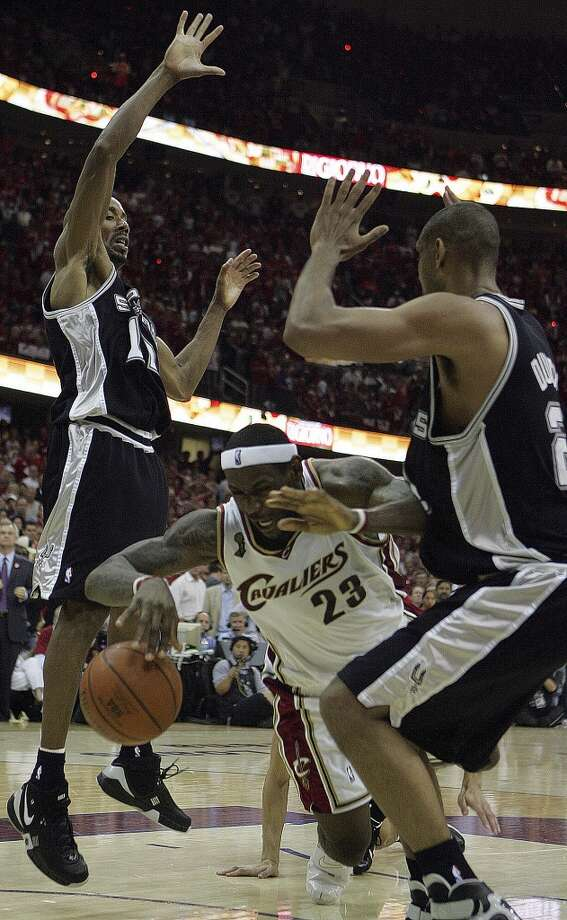 The Cavaliers' LeBron James falls between the Spurs' Bruce Bowen and Tim Duncan after being fouled by Manu Ginobili (not pictured) during second half action of Game 3 in the NBA Finals at the Quicken Loans Arena on June 12, 2007, in Cleveland.