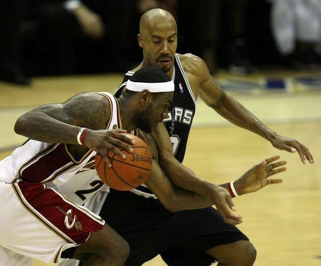 Cavaliers forward LeBron James (23) looks for room around Spurs forward Bruce Bowen (12) late in Gam