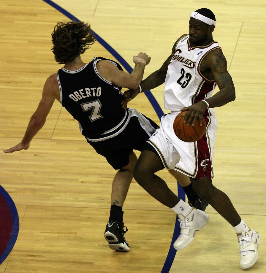 Cavaliers forward LeBron James (23) looks for room around Spurs forward Fabricio Oberto (7) during first half action of Game 3 in the NBA Finals at the Quicken Loans Arena on June 12, 2007, in Cleveland.