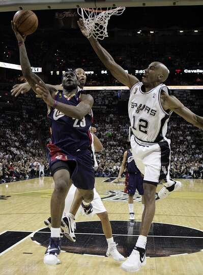 The Spurs' Robert Horry and Bruce Bowen defend the Cavaliers' LeBron James during first half action