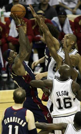 Cavaliers forward LeBron James (23) shoots against the defense of Spurs forward Tim Duncan (21), for
