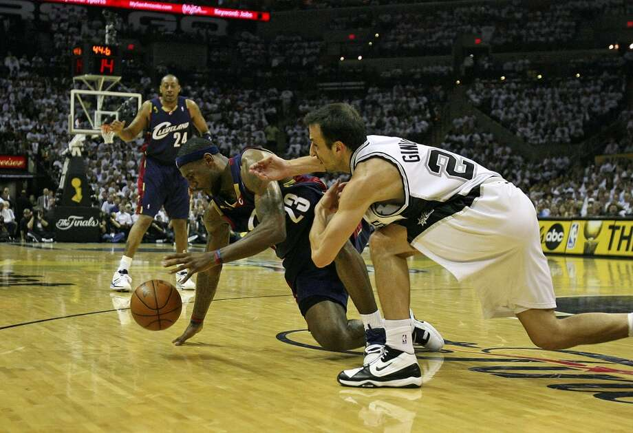 Spurs guard Manu Ginobili (20) and Cavaliers forward LeBron James (23) compete for the loose ball during first half action in the NBA Finals Game 1 in San Antonio on June 7, 2007.