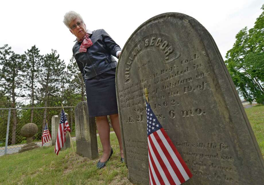 Nancy Morris looks over the grave stone, June 10, 2013,  of Civil War soldier William H. Secor, a Halfmoon resident who died in the Battle of Antietam and who is buried in the Clifton Park Cemetery in Halfmoon, N.Y.   (Skip Dickstein/Times Union) Photo: SKIP DICKSTEIN / 00022751A