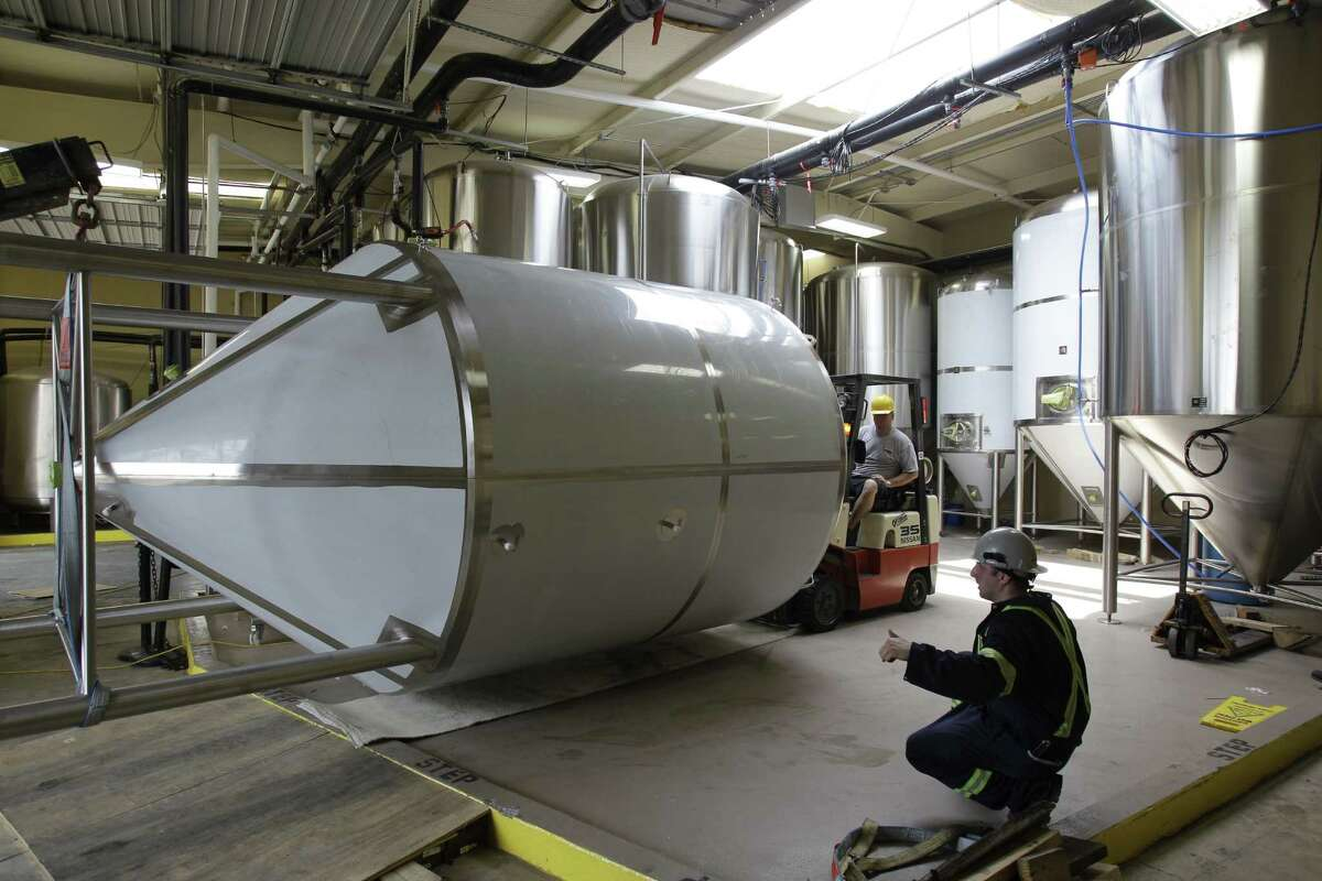 Jason Herring, left, with Karbach Brewing Co., and Josh Wolf with Newlands Systems position a 90-barrel fermenting tank for Karbach.