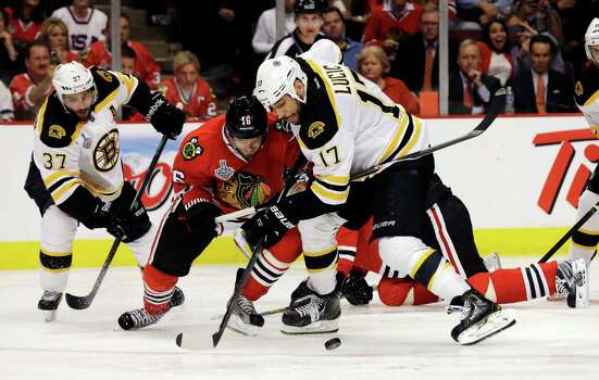 Chicago Blackhawks center Marcus Kruger (16) and Boston Bruins left wing Milan Lucic (17) battle for the control of the puck during the third period of Game 1 in their NHL Stanley Cup Final hockey series, Wednesday, June 12, 2013, in Chicago. (AP Photo/Nam Y. Huh) Photo: Nam Y. Huh, Associated Press / AP