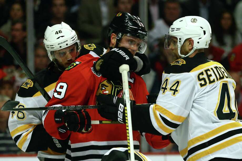 CHICAGO, IL - JUNE 12:  Jonathan Toews #19 of the Chicago Blackhawks is held by David Krejci #46 and Dennis Seidenberg #44 of the Boston Bruins in Game One of the NHL 2013 Stanley Cup Final at United Center on June 12, 2013 in Chicago, Illinois. Photo: Bruce Bennett, Getty Images / 2013 Getty Images