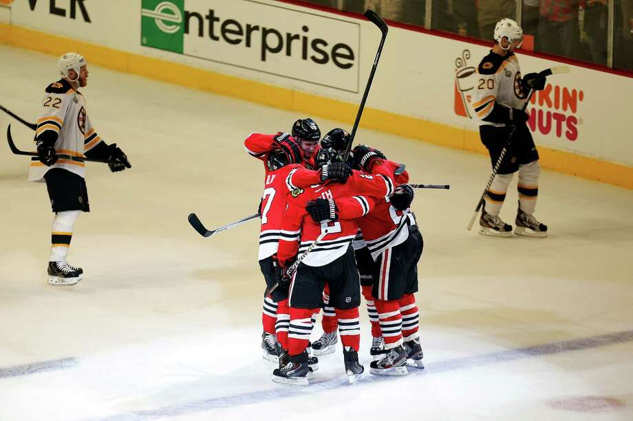 CHICAGO, IL - JUNE 12:  Johnny Oduya (R) #27 of the Chicago Blackhawks celebrates with teammates after he scored a goal in the third period against the Boston Bruins in Game One of the 2013 NHL Stanley Cup Final at United Center on June 12, 2013 in Chicago, Illinois. Photo: Gregory Shamus, Getty Images / 2013 Getty Images