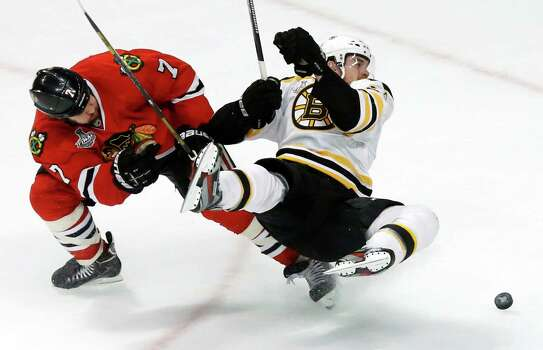 Boston Bruins left wing Daniel Paille, right, shoots as he collides with Chicago Blackhawks defenseman Brent Seabrook during the third period of Game 1 in their NHL Stanley Cup Final hockey series on Wednesday, June 12, 2013, in Chicago. (AP Photo/Charles Rex Arbogast) Photo: Charles Rex Arbogast, Associated Press / AP