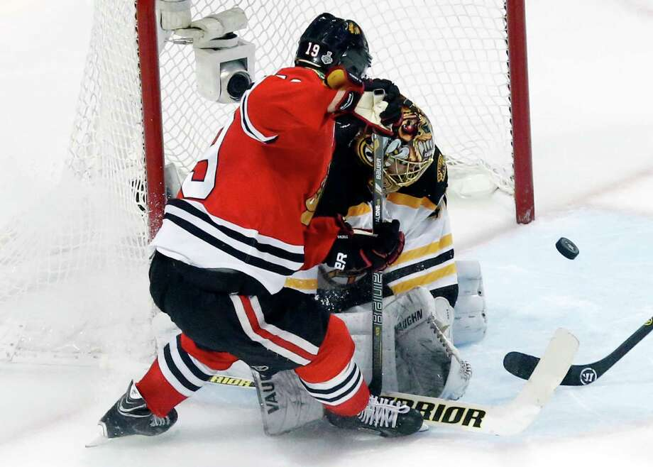 Boston Bruins goalie Tuukka Rask, right, blocks a shot by Chicago Blackhawks center Jonathan Toews (19) during the third period of Game 1 in their NHL Stanley Cup Final hockey series on Wednesday, June 12, 2013, in Chicago. (AP Photo/Charles Rex Arbogast) Photo: Charles Rex Arbogast, Associated Press / AP