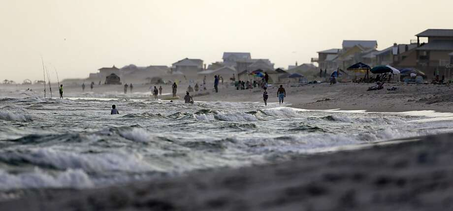 Tourists play in the water of the Gulf of Mexico as they summer in Gulf Shores, Ala., on Tuesday, June 11, 2013. (AP Photo/Dave Martin) Photo: Dave Martin, Associated Press