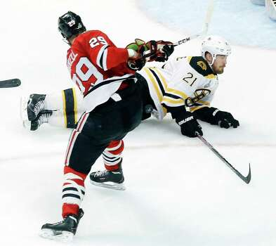 Boston Bruins defenseman Andrew Ference (21) blocks a shot by Chicago Blackhawks left wing Bryan Bickell (29) during the second period of Game 1 in their NHL Stanley Cup Final hockey series on Wednesday, June 12, 2013, in Chicago. (AP Photo/Charles Rex Arbogast) Photo: Charles Rex Arbogast, Associated Press / AP