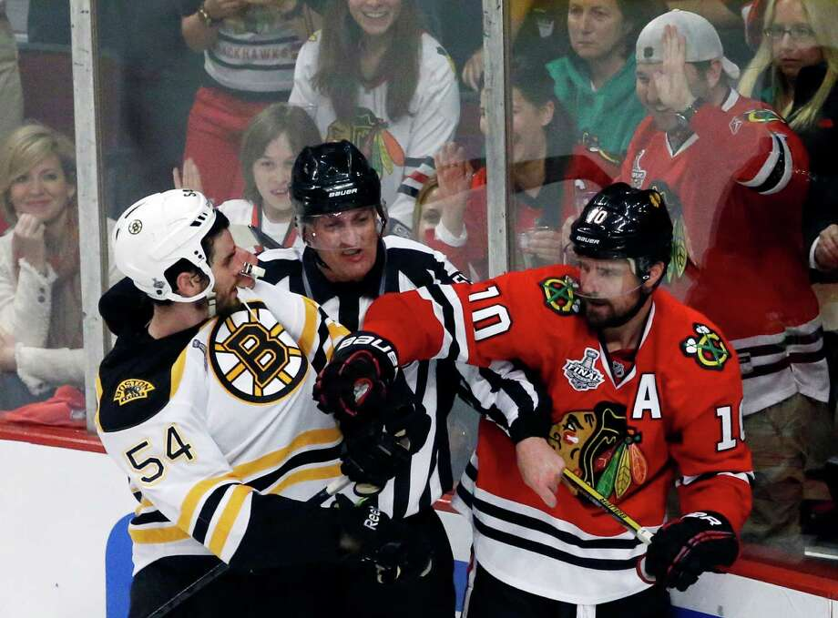 A referee tries to break up a fight as Boston Bruins defenseman Adam McQuaid (54) goes after Chicago Blackhawks center Patrick Sharp (10) during the second period of Game 1 in their NHL Stanley Cup Final hockey series,Wednesday, June 12, 2013 in Chicago. (AP Photo/Charles Rex Arbogast) Photo: Charles Rex Arbogast, Associated Press / AP