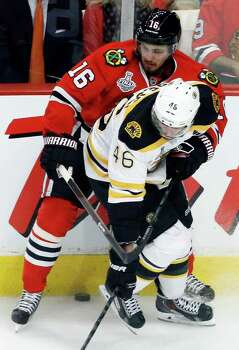 Boston Bruins center David Krejci (46) and Chicago Blackhawks center Marcus Kruger (16) battle for the control of the puck during the second period of Game 1 in their NHL Stanley Cup Final hockey series on Wednesday, June 12, 2013, in Chicago. (AP Photo/Charles Rex Arbogast) Photo: Charles Rex Arbogast, Associated Press / AP