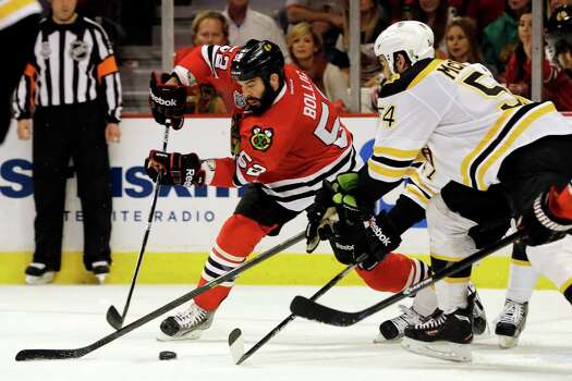 Chicago Blackhawks left wing Brandon Bollig (52) controls the puck against Boston Bruins defenseman Adam McQuaid (54) and Torey Krug during the second period of Game 1 in their NHL Stanley Cup Final hockey series, Wednesday, June 12, 2013, in Chicago. (AP Photo/Nam Y. Huh) Photo: Nam Y. Huh, Associated Press / AP
