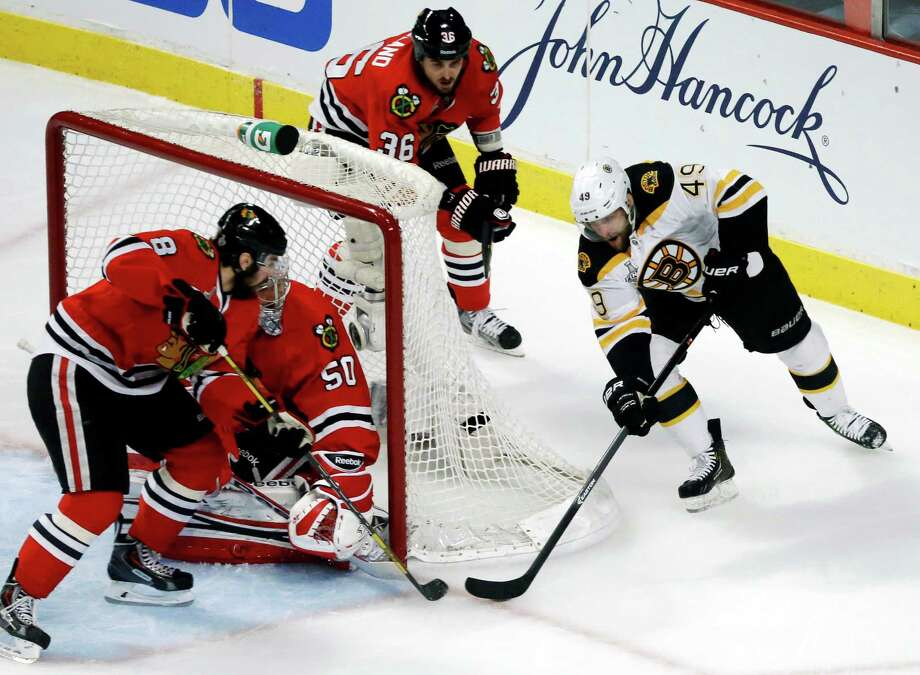 Chicago Blackhawks defenseman Nick Leddy (8) and goalie Corey Crawford (50) make a save on a shot by Boston Bruins center Rich Peverley (49) during the first period of Game 1 in their NHL Stanley Cup Final hockey series,Wednesday, June 12, 2013 in Chicago. (AP Photo/Charles Rex Arbogast) Photo: Charles Rex Arbogast, Associated Press / AP