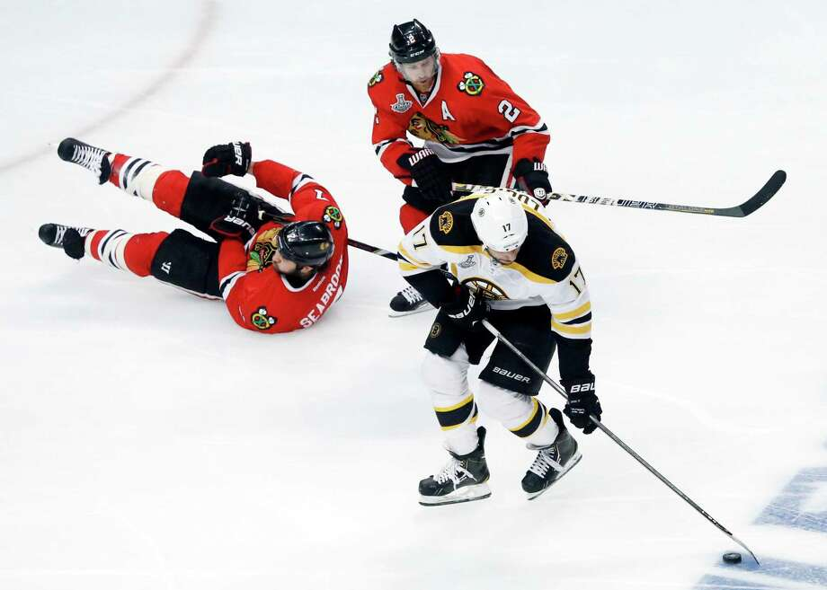 Boston Bruins left wing Milan Lucic (17) controls the puck against Chicago Blackhawks defensemen Brent Seabrook (7) and Duncan Keith (2) during the second period of Game 1 in their NHL Stanley Cup Final hockey series on Wednesday, June 12, 2013, in Chicago. (AP Photo/Charles Rex Arbogast) Photo: Charles Rex Arbogast, Associated Press / AP