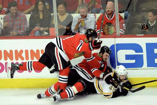 CHICAGO, IL - JUNE 12:  (L-R) Brandon Saad #20 and Dave Bolland #36 of the Chicago Blackhawks fall on top of Rich Peverley #49 of the Boston Bruins in the first period of Game One of the 2013 NHL Stanley Cup Final at United Center on June 12, 2013 in Chicago, Illinois. Photo: Harry How, Getty Images / 2013 Getty Images