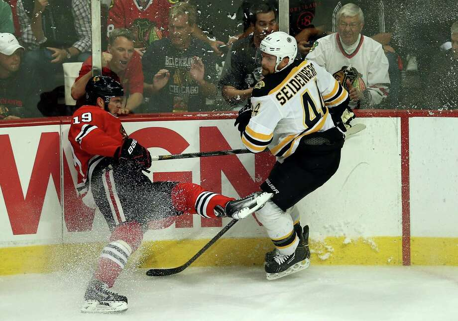 CHICAGO, IL - JUNE 12:  Jonathan Toews #19 of the Chicago Blackhawkscrashes into the boards in the second period against the Dennis Seidenberg #44 of the Boston Bruins in Game One of the 2013 NHL Stanley Cup Final at United Center on June 12, 2013 in Chicago, Illinois. Photo: Jonathan Daniel, Getty Images / 2013 Getty Images