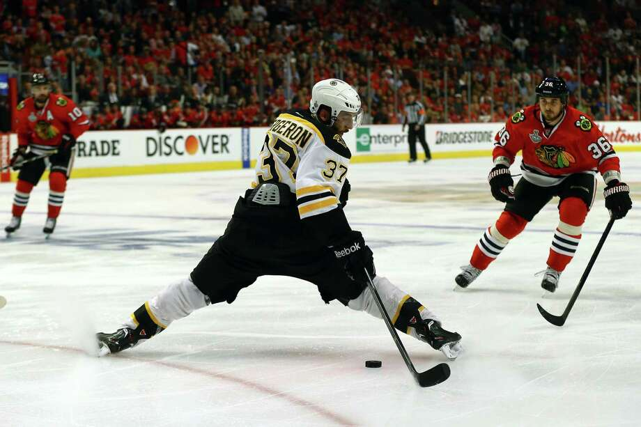 CHICAGO, IL - JUNE 12:  Patrice Bergeron #37 of the Boston Bruins attempts to control the puck in the second period against  Dave Bolland #36 of the Chicago Blackhawks in Game One of the NHL 2013 Stanley Cup Final at United Center on June 12, 2013 in Chicago, Illinois. Photo: Bruce Bennett, Getty Images / 2013 Getty Images