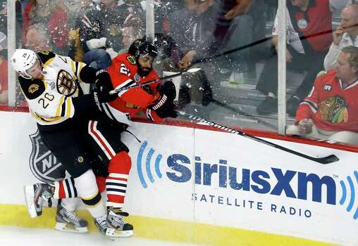 Boston Bruins left wing Daniel Paille (20) and Chicago Blackhawks defenseman Johnny Oduya (27) collide during the first period of Game 1 in their NHL Stanley Cup Final hockey series on Wednesday, June 12, 2013, in Chicago. (AP Photo/Charles Rex Arbogast) Photo: Charles Rex Arbogast, Associated Press / AP